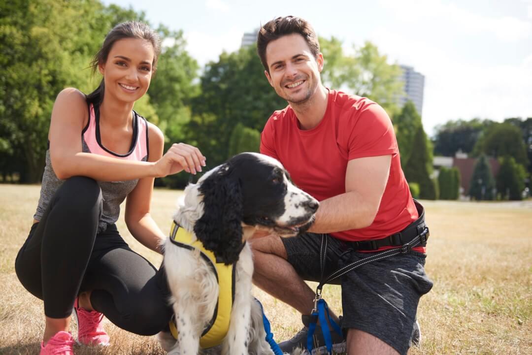 Un couple souriant félicitant leur chien de son exercice de Canicross